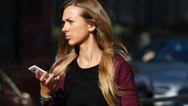 A woman uses her mobile phone on the high street in central London