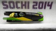 Ein jamaikanisches Gespann rast bei den Olympischen Spielen 2014 durch den Eiskanal von Sotschi.