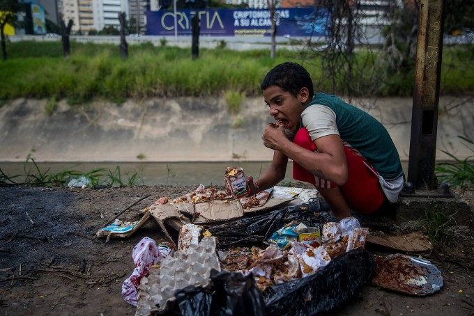 Ein Junge un Caracas vor einem Müllsack aus einer Bäckerei