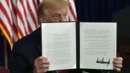 Präsident Donald Trump hält im Trump National Golf Club eine unterzeichnete Verfügung hoch.