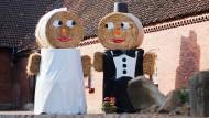 Wer macht hier große Augen? Zwei Strohfiguren mit Hochzeitskleid und Anzug werfen sich auf einem Hof in Lüdersen verliebte Blicke zu.