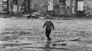 Alan Parks' Glasgow der Siebziger: Ein Junge spielt in einem verfallenen Gelände in einer Pfütze.