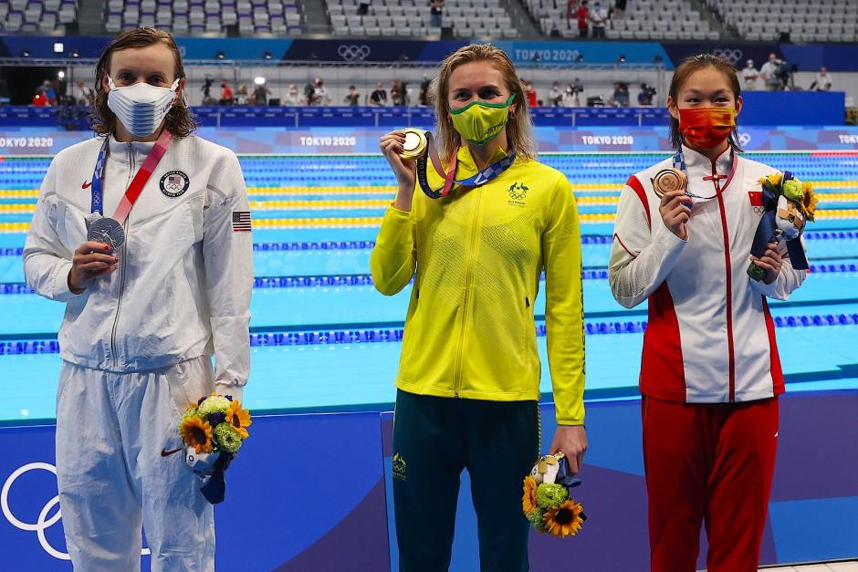Ariarne Titmus (m.) präsentiert ihre Goldmedaille in Tokio.
