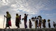 Weltweit sind rund rund 68,5 Millionen Menschen auf der Flucht. Hier gehen Rohingya-Flüchtlinge mit ihrem Gepäck über ein Reisfeld in Bangladesch.