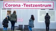 Menschen warten vor dem Corona-Testzentrum am Helios-Klinikum in Schwerin.