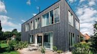 Ein Gebäude wie eine Wundertüte: In dem kompakten Baukörper, der aussieht wie ein Einfamilienhaus, stecken drei Wohneinheiten.