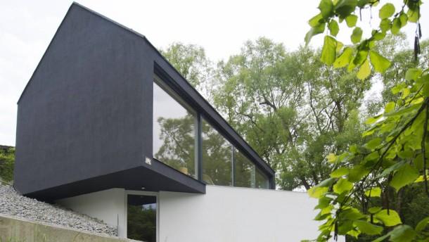 Neue Architektur - Das kleine Wohnhaus nahe einer Burg dient Thomas Jäger auch als Büro und erhält seine ungewöhnliches Aussehen durch die Form eines  Kubus, auf dem ein zweites Stockwerk mit Satteldach leicht verdreht sitzt.