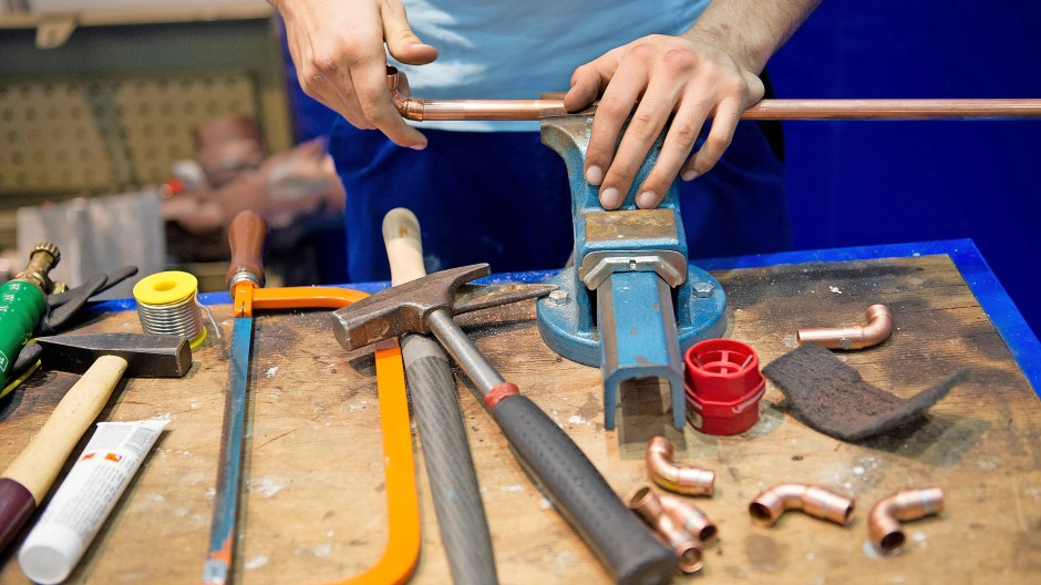 Fingerfertig: Ein Installateur  bearbeitet ein Rohr.