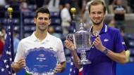 Der US-Open-Gewinner Daniil Medwedew (r.) und der Zweite Novak Djokovic posieren mit ihren Trophäen.