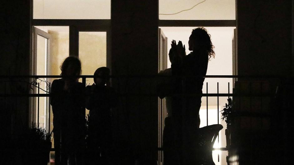 Bewohner eines Hauses in Köln stehen im März 2020 auf ihrem Balkon und klatschen Beifall für Mitarbeiter im Gesundheitswesen.
