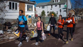 New York City Marathon runners carry relief supplies through a damaged neighborhood in the Staten Island borough of New York