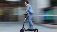 Ein Mann fährt mit einem Elektro-Roller in Bamberg.