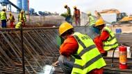 Bauarbeiter schweißen Stahlstangen auf der Baustelle einer Straße in Shekou & Qianhai Freihandelszone zusammen.