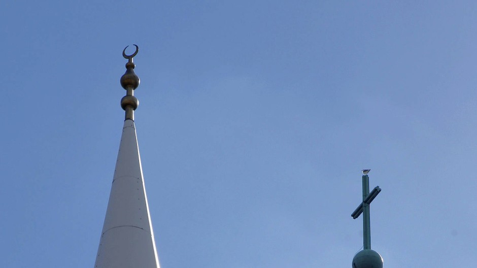 Die Spitze des Minarett der Yavus Sultan Selim Moschee (l) mit dem Halbmond und das Kreuz auf der Kirchturmspitze der Liebfrauenkirche (r)