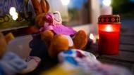 Zwei Stofftiere und Kerzen schmücken die Gedenkstätte vor der Kita.