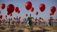 """Rio de Janeiro: Die Nichtregierungsorganisation """"Rio de Paz"""" platzierte zum Gedenken der Opfer der Covid-19-Pandemie 1000 rote Luftballons und 100 Kreuze am Strand der Copacabana."""