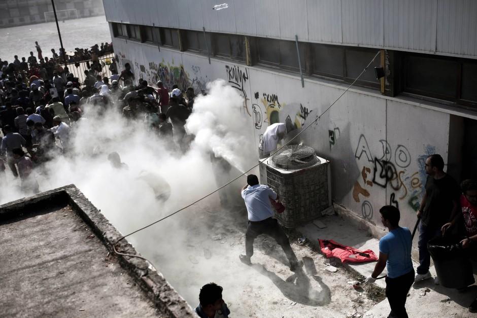 Ein Polizist versucht eine Massenhysterie unter den Flüchtlingen in Kos
