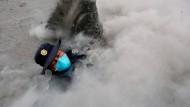 Ein Polizisten versinkt im Rauch des Vulkans.