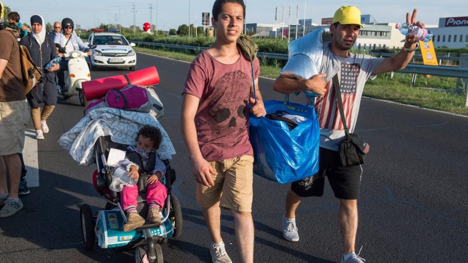 Flüchtlinge laufen in der Nähe von Budapest über eine Straße in Richtung Österreich.