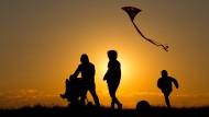 Familienspaziergang im Sonnenuntergang: Glück lässt sich offenbar besser genießen, wenn das Einkommen stimmt.