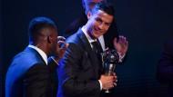 Cristiano Ronaldo posiert nach seiner Auszeichnung zum Weltfußballer mit der Trophäe.