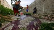 Brutaler Alltag: Familienangehörige in Honduras säubern säubern eine Gasse vom Blut eines Mordopfers.