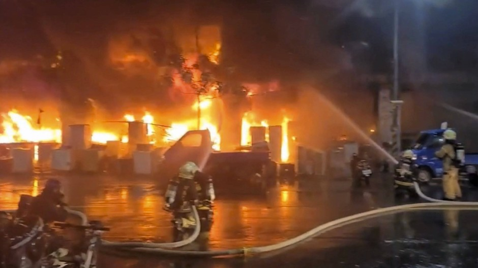 Feuerwehrleute bei den Löscharbeiten des Gebäudebrandes. Das Feuer hat in der Nacht ein 13-stöckiges Gebäude im Süden Taiwans verschlungen.