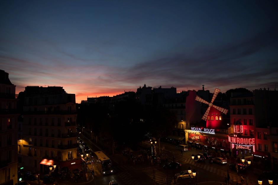 Das Moulin Rouge vor einem herbstlichen Pariser Abendhimmel.