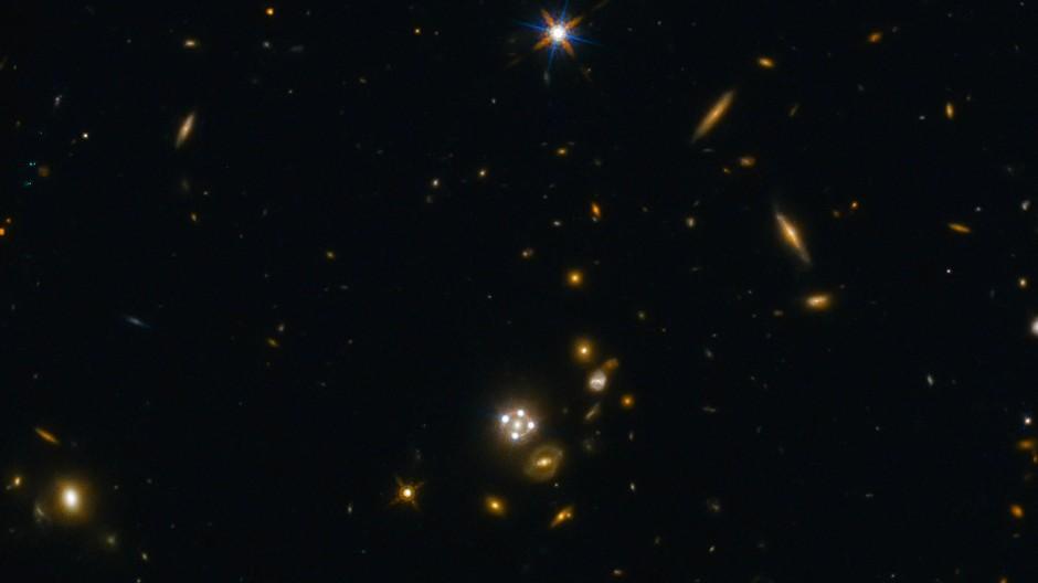 Der Quasar HE0435-1223 in der Bildmitte wird durch den Gravitationslinseneffekt einer Vordergrundgalaxie in mehrere Bildpunkte aufgespalten.