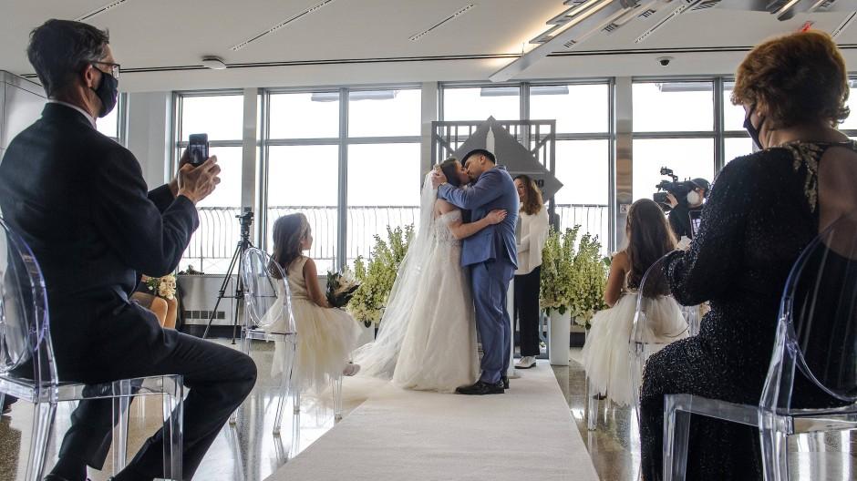 Kristine Mariana (M,l) und Jorge Martinez küssen sich, nachdem sie während ihrer Hochzeits im Empire State Building ihr Gelübde abgelegt haben.