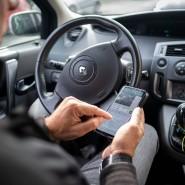 Ein Mann schreibt auf einem Smartphone im Auto (Symbolbild)