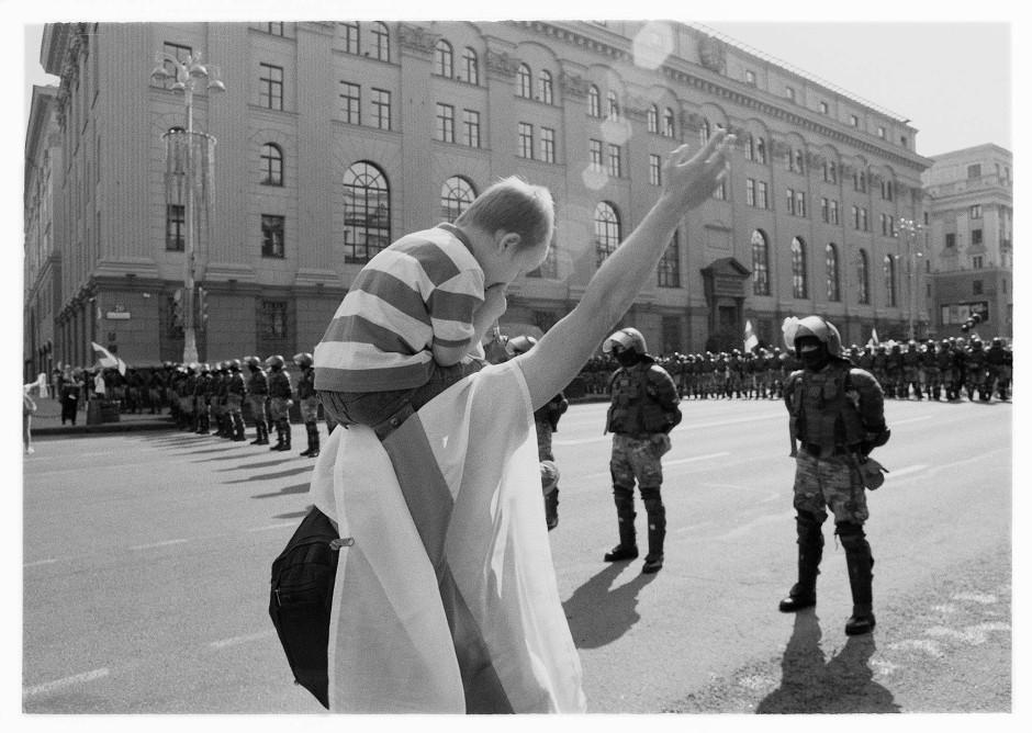 Die Staatsmacht im Bunkermodus: Ein Demonstrant mit Kind begrüßt die Maskierten.
