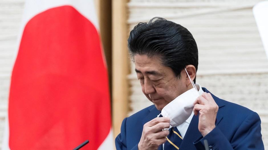 Japans Regierungschef Abe nimmt während einer Pressekonferenz vergangenen Dienstag seinen Mundschutz ab.