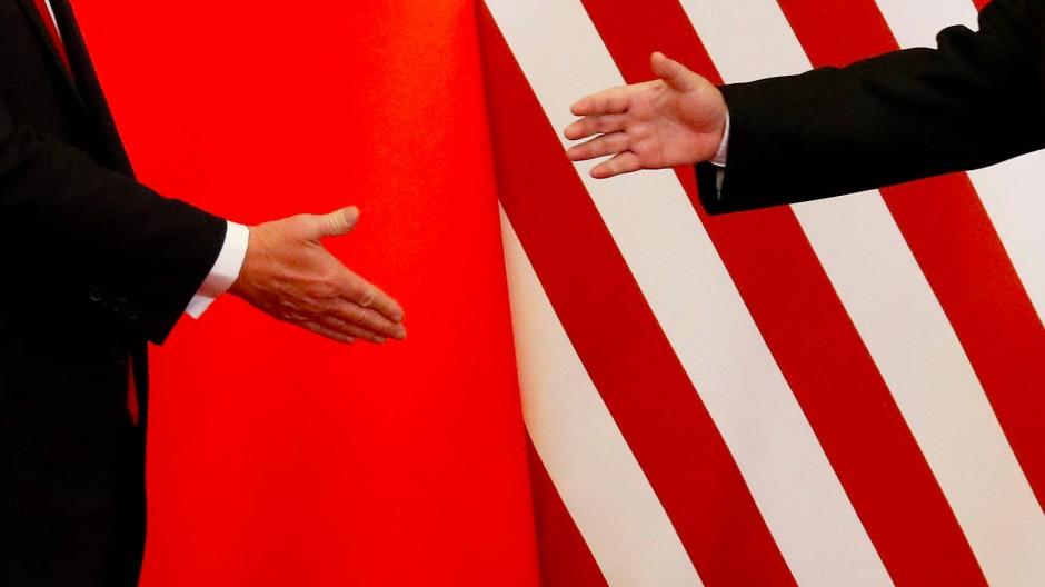 Der amerikanische Präsident Donald Trump und Chinas Staatspräsident Xi Jinping geben sich im Novemeber 2017 in Peking die Hand.