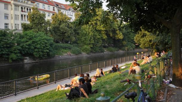 Berlin, Deutschland, junge Leute sitzen bei Sonnenuntergang am Ufer des Landwehrkanals am Maybachufer