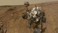 """Was guckst du? Die Sonde """"Curiosity"""" auf dem versteinerten Grund eines Sees auf dem Mars. Das Bild ist ein Selfie des Gefährts, auf dem der Kameraarm herausretouchiert wurde."""