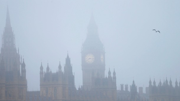 A bird flies past the Houses of Parliament on a foggy autumn morning in central London