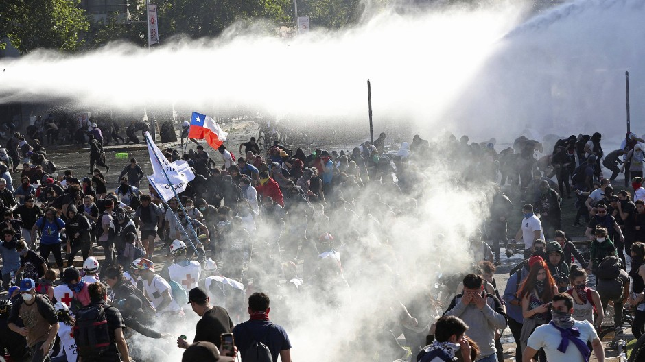 Die Polizei feuert vergangenen Sonntag Wasserwerfer auf Demonstranten in der Hauptstadt Santiago.