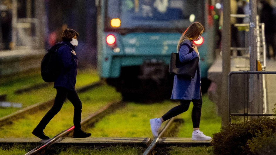 Zwei junge Frauen mit Mund-Nasen-Schutz an einer U-Bahnstation in Frankfurt.