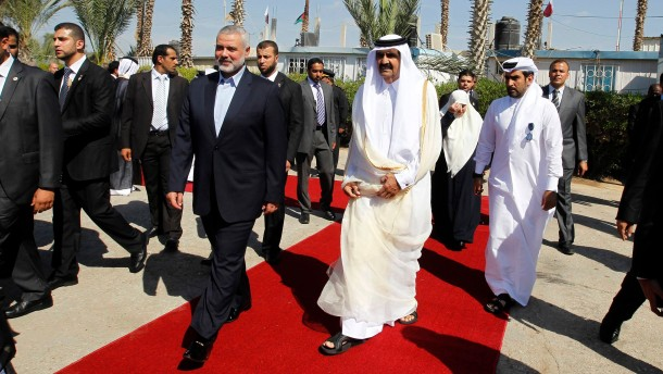 Hamas Prime Minister Haniyeh walks with the Emir of Qatar  in Rafah