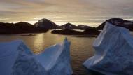 Eisberge treiben bei Sonnenaufgang in der Nähe von Kulusuk auf dem Wasser.