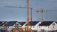 Baukräne stehen auf einem Baugrundstück neben neugebauten Wohnhäusern in Köln.