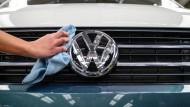 Eine Mitarbeiterin putzt das VW-Logo eines T6 von Volkswagen.