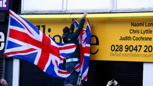 Loyalists hang Union flags during a protest outside the offices of a member of the Alliance Party in east Belfast