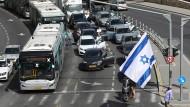 Auf einer Hauptstraße in Jerusalem verharren Menschen am 8. April schweigend, während Sirenen ertönen.