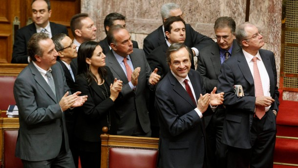 Greek Prime Minister Samaras and parliamentarians applaud after a vote for the 2013 budget at the parliament in Athens