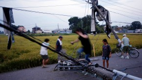 Residents walk over fallen power poles damaged by what seemed to be a tornado in Koshigaya