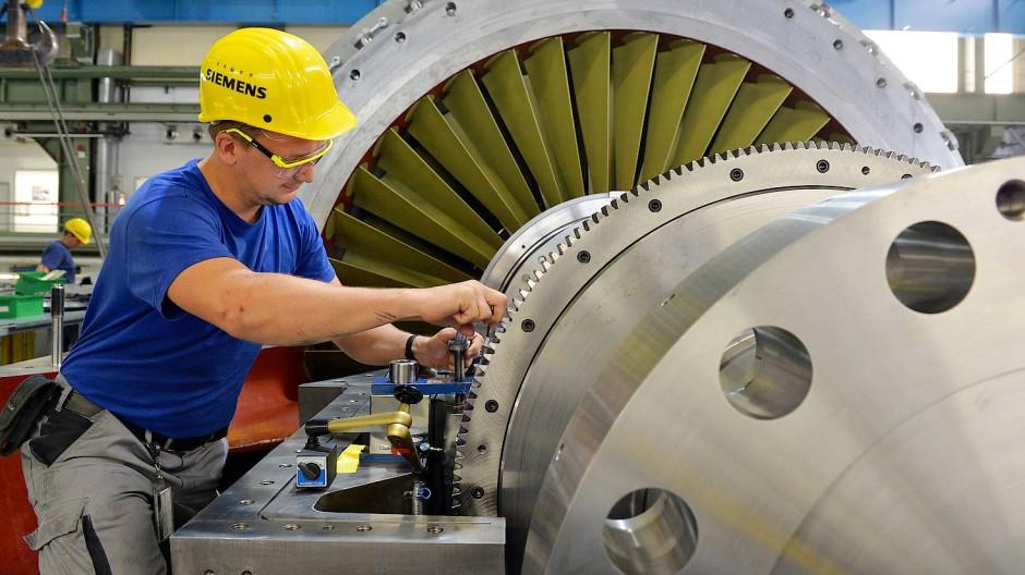 Ein Siemens-Mitarbeiter arbeitet an einer Turbine.