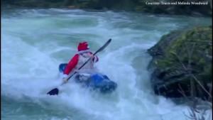 Verkleideter Weihnachtsmann paddelt durch Stromschnellen