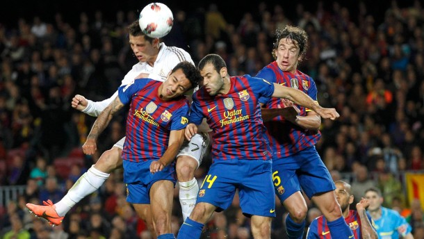 "Real Madrid's Ronaldo heads the ball with Barcelona's Thiago, Mascherano and Puyol during their Spanish first division ""El Clasico"" soccer match in Barcelona"